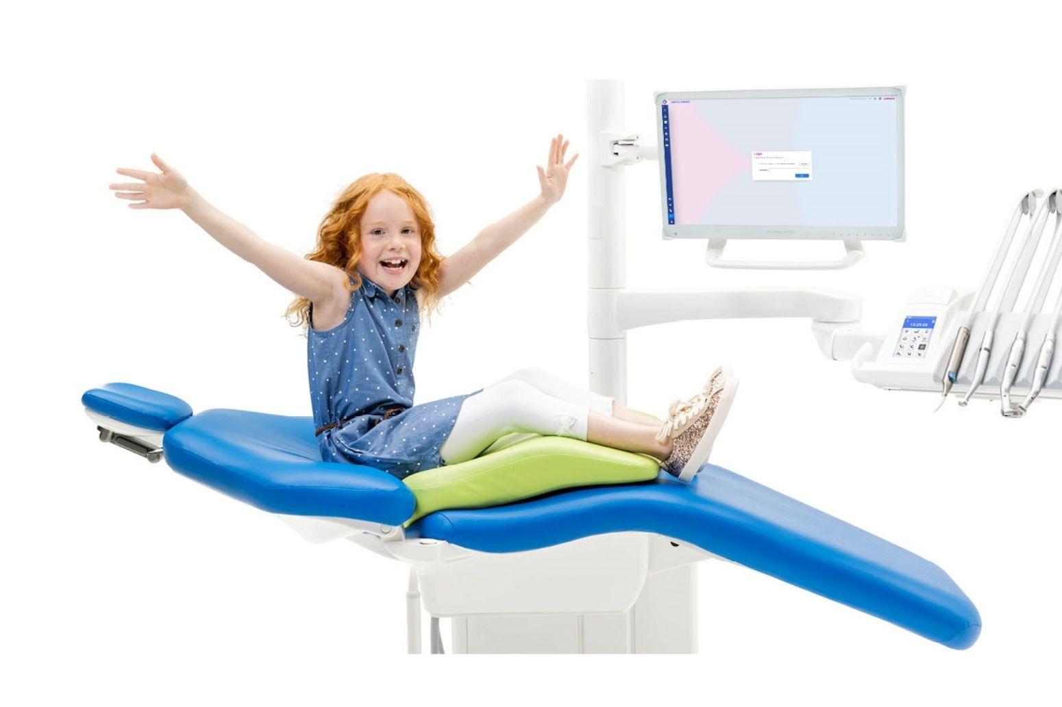Glad pige sidder med armene udstrakt på en tandlæge unit og hun har en pude under sig, så hun sidder ergonomisk korrekt